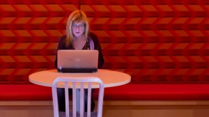 Woman working at table under red light