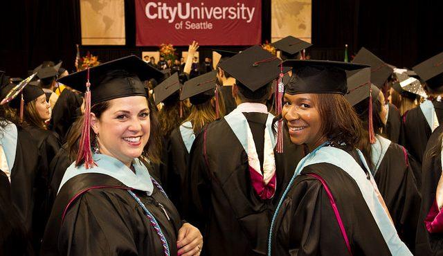Two graduates acknowledge the camera