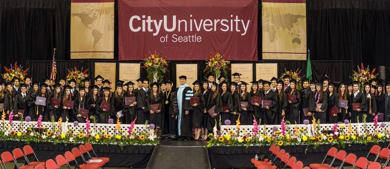 CityU commencement ceremony with large group of graduates on stage