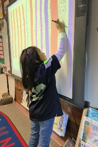 Vaughan's student writes on a smartboard