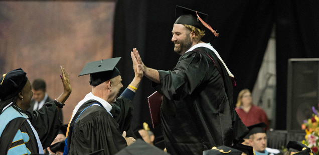 Faculty high-five a graduate