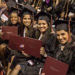 CityU Graduates Smiling while holding diplomas
