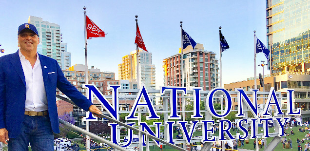 Chancellor Cunningham in front of the National University sign at Petco Park in San Diego, CA.