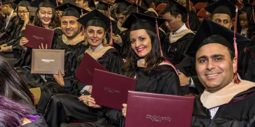 CityU Graduates smiling with diplomas