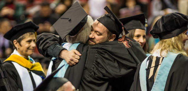 Graduate hugs a faculty member