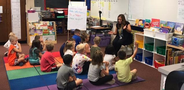 First grade teacher with students in a classroom.