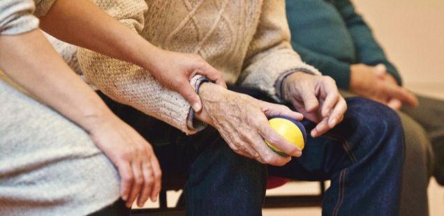 Woman holds elderly man's hand