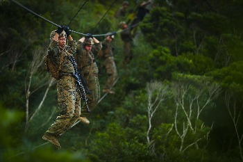 U.S Marines with Bravo Company, 1st Battalion, 3rd Marine Regiment, move along a rope obstacle during the endurance course, aboard Camp Gonsalves, Okinawa, Japan, July 7, 2017.