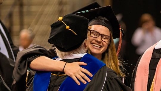 Professor hugs a student at graduation