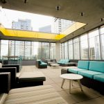 20th-floor deck featuring open ceiling, multiple patio couches, and large bar table